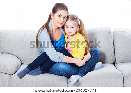 Mother with daughter sitting on sofa with embrace, smiling , happy.