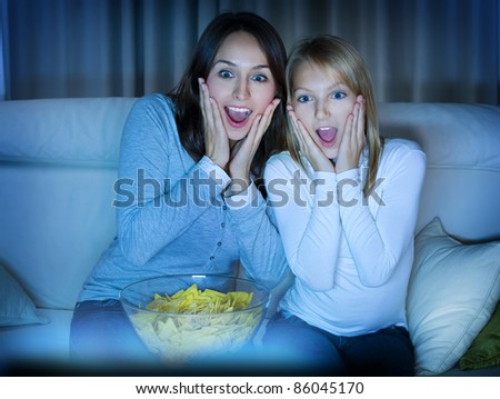 Mother with Daughter watching TV .True Emotions - stock photo