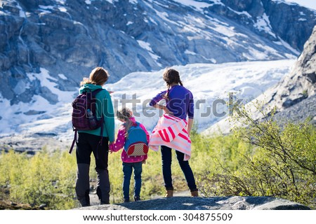 mother with daughters are hiking at the mountains and looking at the glacier