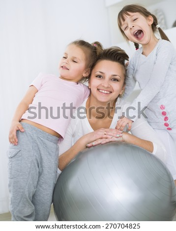 Mother with daughters doing gymnastic exercises with balls - stock photo