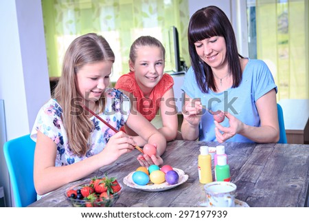 Mother with daughters preparing eggs for Easter at home