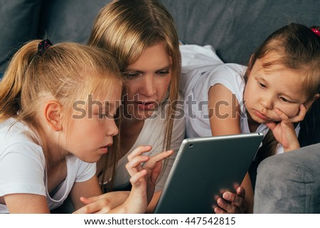 Mother with daughters using laptop surfing internet. Family portrait. Lifestyle