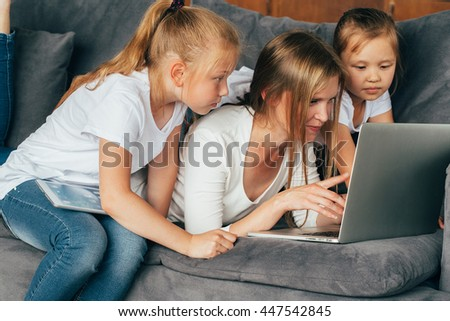 Mother with daughters using laptop surfing internet. Family portrait. Lifestyle  - stock photo