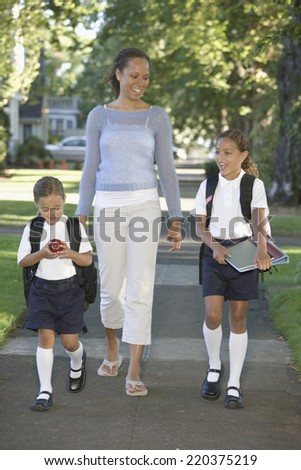 Mother with daughters walking down sidewalk - stock photo