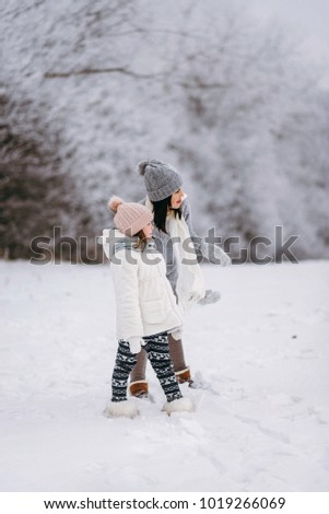 Mother with daughters walking in winter park. Woman hugging girl in winter