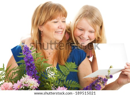 Mother with flowers and a card from her daughter.  Birthday or Mother's Day concept.   - stock photo