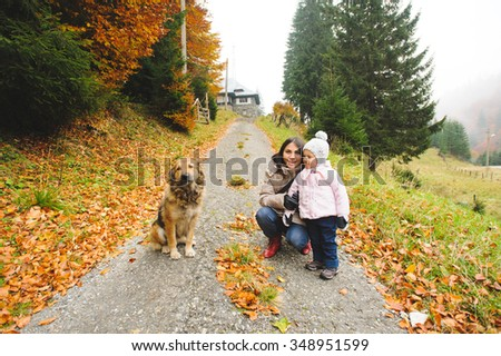 mother with girl and dog on road - stock photo