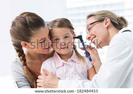 Mother with girl being examined by female doctor with otoscope in clinic - stock photo