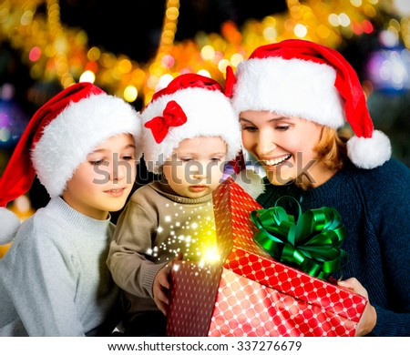 Mother with happy children opens the box with christmas gifts on the new year  holiday - indoors - stock photo