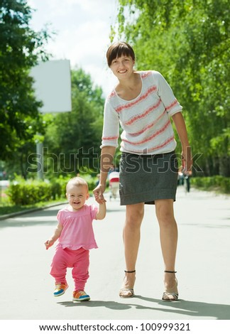 mother with happy toddler walking on road
