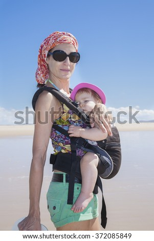 mother with headscarf green shorts carrying her one year baby with pink hat in front rucksack walking at a beach - stock photo