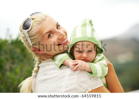 Mother with her adorable baby outdoors - stock photo