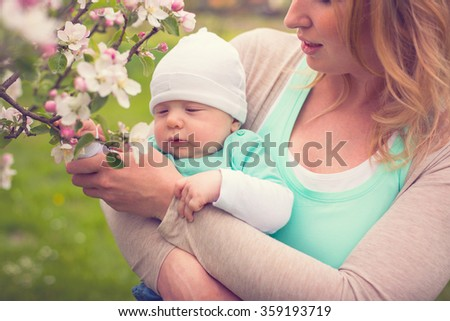 mother with her baby boy holding blooming branch - stock photo