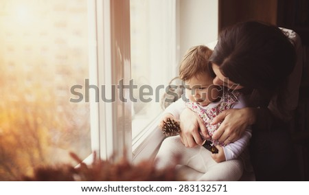 Mother with her baby daughter by the window - stock photo