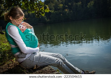 mother with her baby in a sling - stock photo