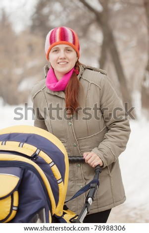 mother with her baby in pram walking at winter park - stock photo