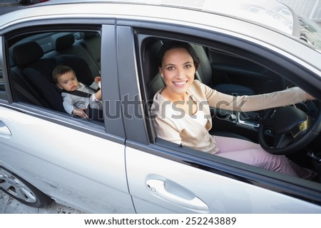 Mother with her baby in the car seat in the car - stock photo