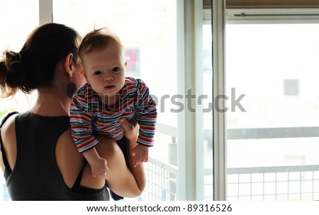 mother with her baby near the window - stock photo