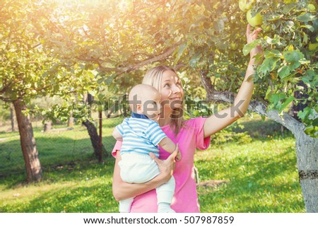 Mother with her baby picking apples from an apple tree
