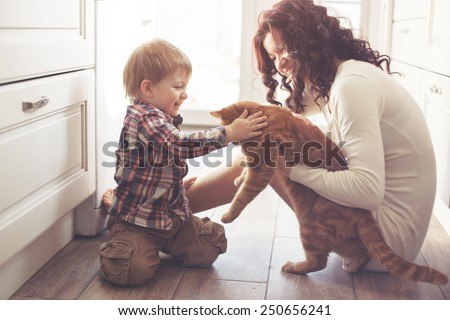 Mother with her baby playing with pet on the floor at the kitchen at home - stock photo
