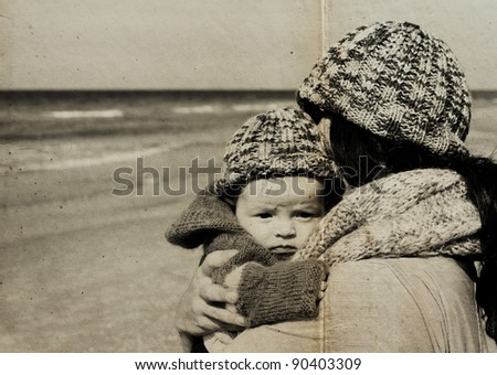 mother with her child on the beach. Photo in old image style. - stock photo