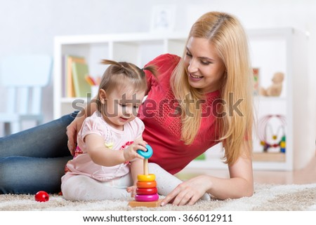 Mother with her child playing with wooden blocks at home - stock photo
