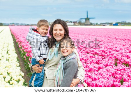 Mother with her child walks between of the white and purple tulips field - stock photo