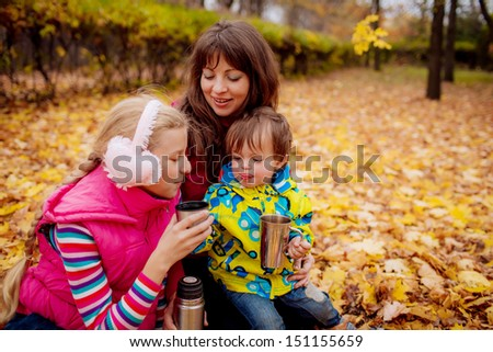mother with her children drink tea in the autumn park. close-up