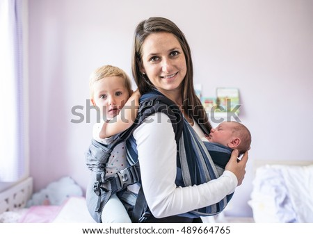 Mother with her children in sling and baby carrier