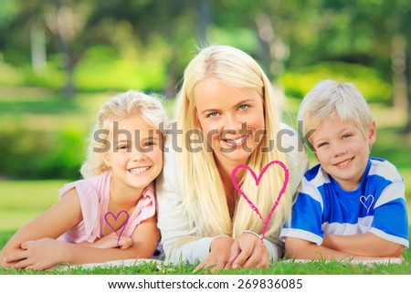 Mother with her children lying down during the summer against valentines love hearts - stock photo