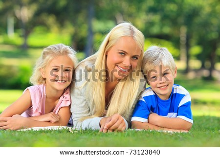 Mother with her children lying down in the park - stock photo