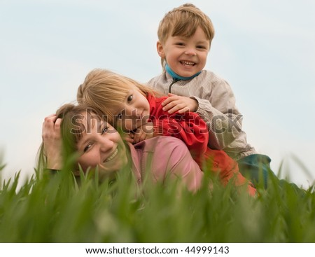 Mother with her children on the green meadow