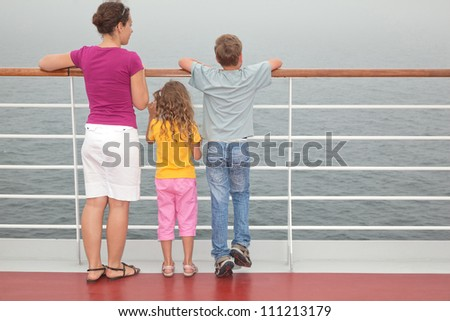 Mother with her children stand on deck of large passenger ship look into sea, full body - stock photo