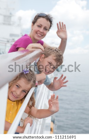 Mother with her children stand on deck of large passenger ship near handrails and waving their hands, focus on daughter - stock photo