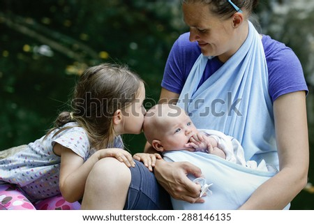 Mother with her daughter and baby in a sling wrap, enjoying active lifestyle in nature, girl kissing the boy on his head. Family values, siblings love and active family lifestyle concepts.  - stock photo