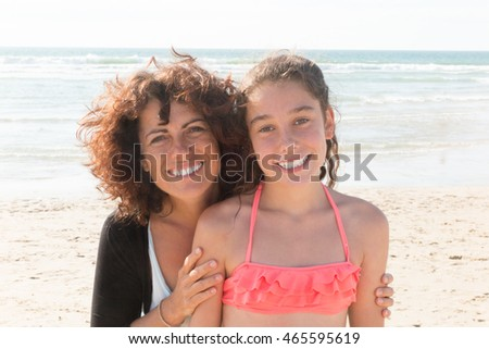 Mother with her daughter at the beach smiling