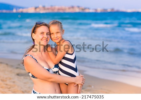 Mother with her daughter at the seashore, happy family concept - stock photo
