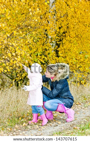 mother with her daughter in autumnal nature - stock photo