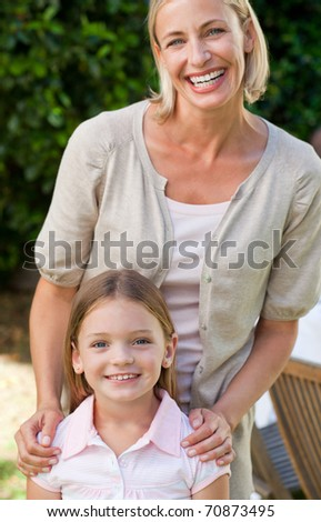 Mother with her daughter looking at the camera in the garden - stock photo