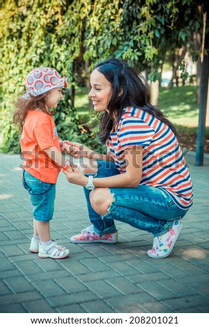 Mother with her daughter playing in the park holding her hands