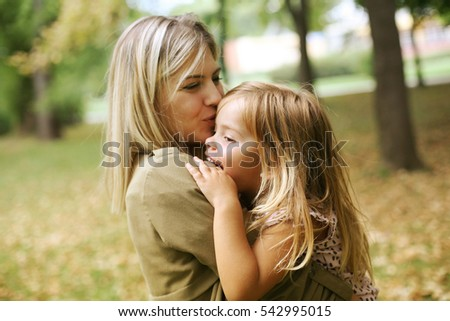 Mother with her daughter playing in the park. Mother hugging her daughter.