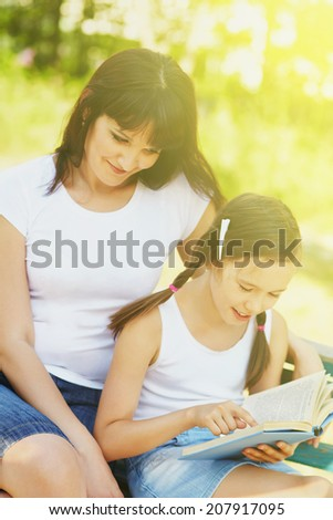 mother with her daughter reading a book in the park - stock photo
