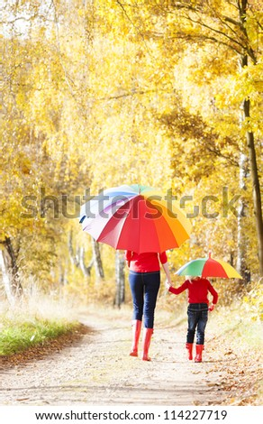 mother with her daughter with umbrellas in autumnal alley - stock photo