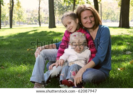mother with her daughters sitting on a grass at the park - stock photo
