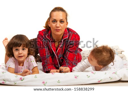 Mother with her kids lying in bed against white background - stock photo