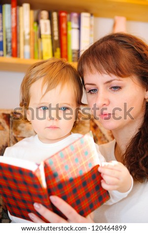 Mother with her little baby son reading book at home - stock photo