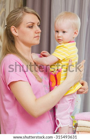 Mother with her little daughter at home - stock photo