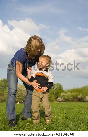 Mother with her little son at sunny day at park