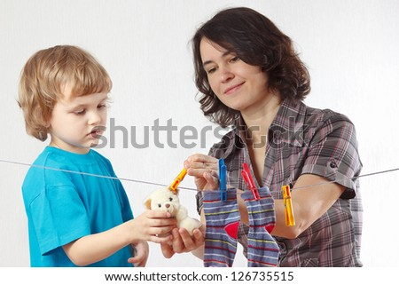 Mother with her little son hanging toy on a white background