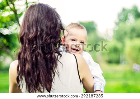 Mother with her little son outdoor in the park - stock photo